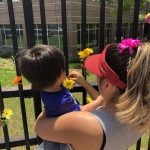 Woman with highlights and red visor helps a child she is holding affix a flower to the fence