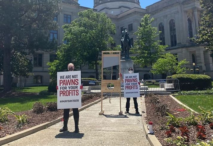 Atlanta DSA members hold up signs and display a DIY mock guillotine in front of the Georgia state capitol on May 1, 2020.